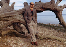 Philip Larkin standing against fallen tree on a pebbled beach